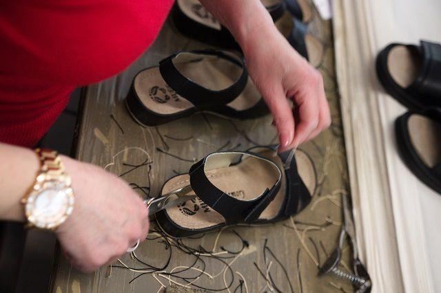 Frau entfernt Fäden von Schuhen